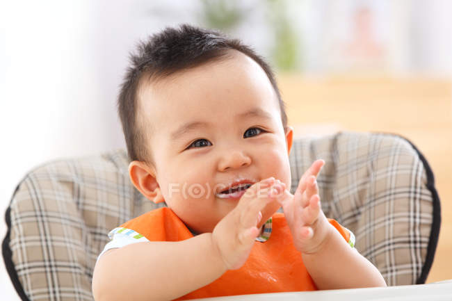Cute happy asian baby boy sitting in chair — Stock Photo