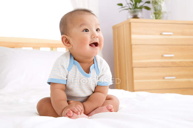 Cute happy asian baby boy sitting on bed and looking away — Stock Photo