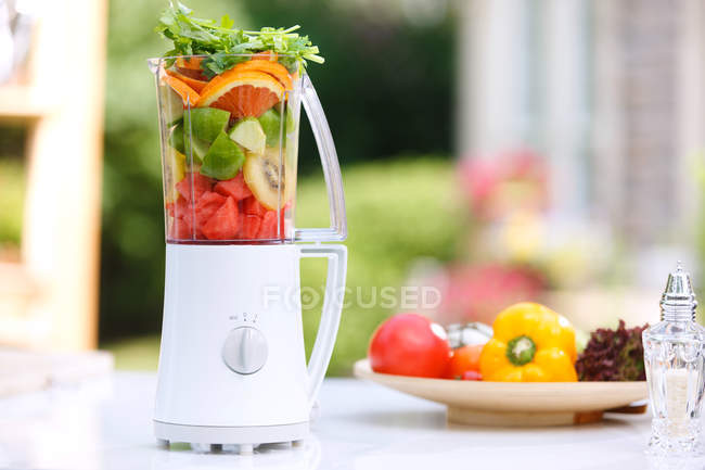 Close-up view of white juicer with ripe fruits and vegetables on table — Stock Photo