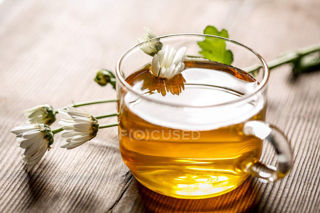Close-up view of healthy organic herbal tea in glass cup and chamomiles on wooden table — Stock Photo