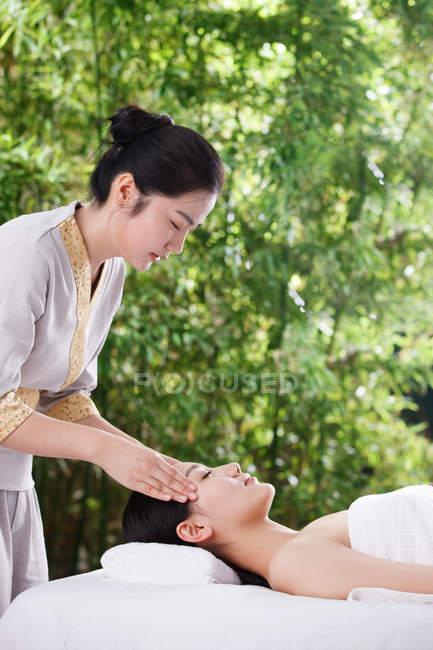 Vista lateral da jovem com os olhos fechados deitado e desfrutar de massagem no spa ao ar livre — Fotografia de Stock