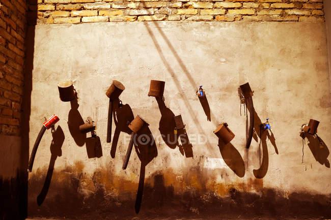 Torneiras de água com sombras na parede marrom no dia ensolarado — Fotografia de Stock