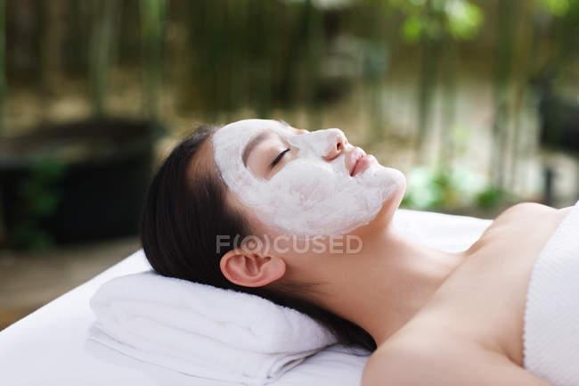 Junge Asiatin mit geschlossenen Augen liegt mit Gesichtsmaske im Outdoor-Spa — Stockfoto