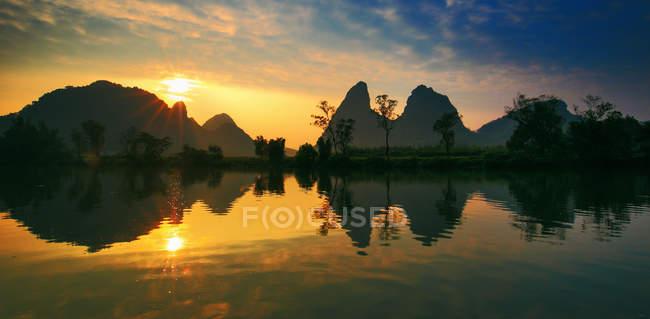 Increíble vista natural de las montañas y la vegetación verde reflejada en el agua al atardecer, Yangshuo, Guilin, China - foto de stock