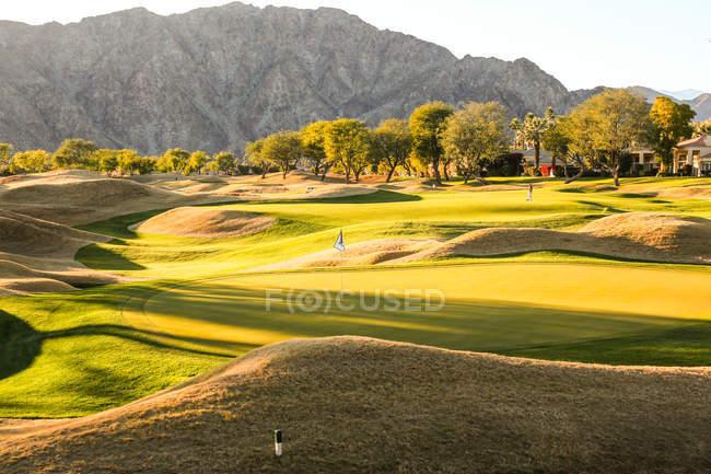 Изумительная зелень на поле для гольфа и красивые горы в солнечный день — стоковое фото