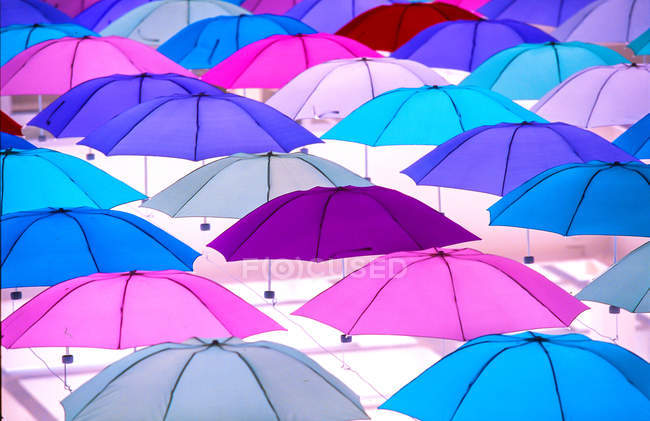 Bright colorful umbrellas hanging on light background, full frame view — стокове фото