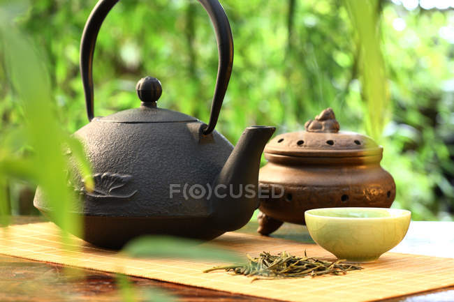 Close-up view of teapot and incense burner on wooden surface, selective focus — Stock Photo