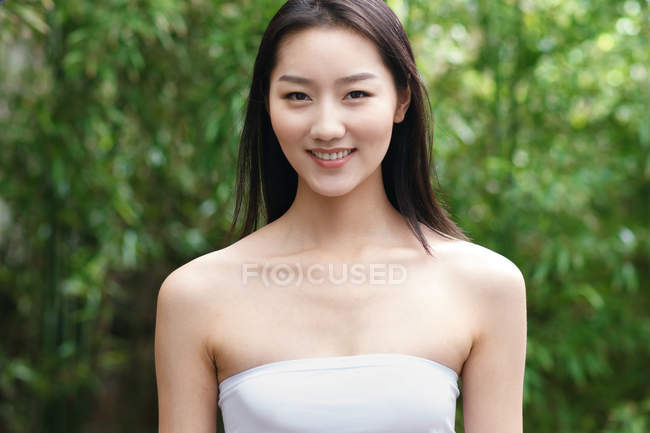 Porträt der schönen jungen brünetten asiatischen Frau, die in die Kamera lächelt — Stockfoto