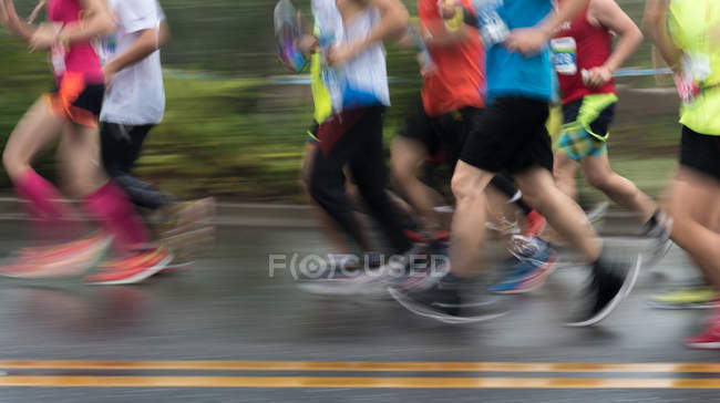 Low section of people running through marathon race, blurred motion — Stock Photo