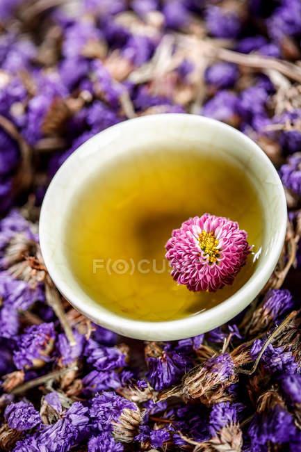 Vue rapprochée d'une tisane bio saine en tasse et fleurs — Photo de stock