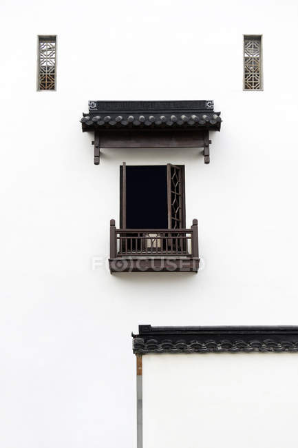 Construção tradicional chinesa com parede branca, pequenas janelas e varanda — Fotografia de Stock