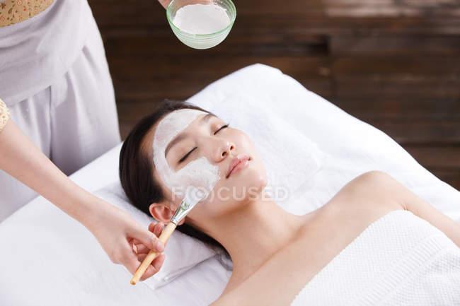 Schnappschuss einer Kosmetikerin, die junge Frau im Spa mit Gesichtsmaske behandelt — Stockfoto