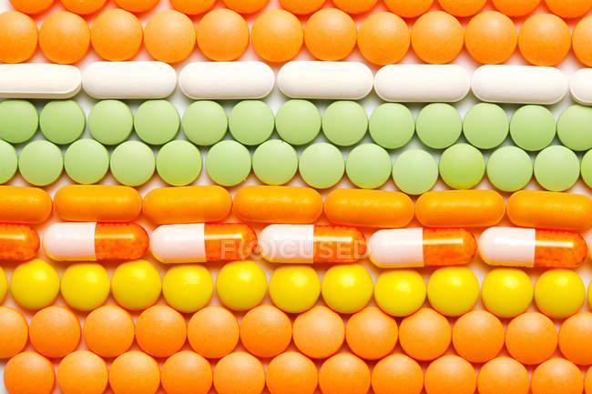 Vista superior de coloridas tabletas y cápsulas medicina fondo - foto de stock