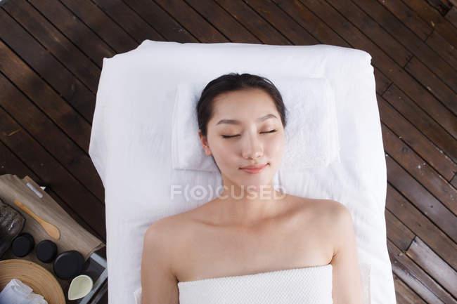Vista dall'alto di bella giovane donna sdraiata con gli occhi chiusi nella SPA all'aperto — Foto stock