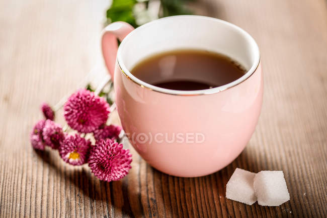 Close-up view of healthy organic herbal tea, pink flowers and sugar on wooden table — Stock Photo