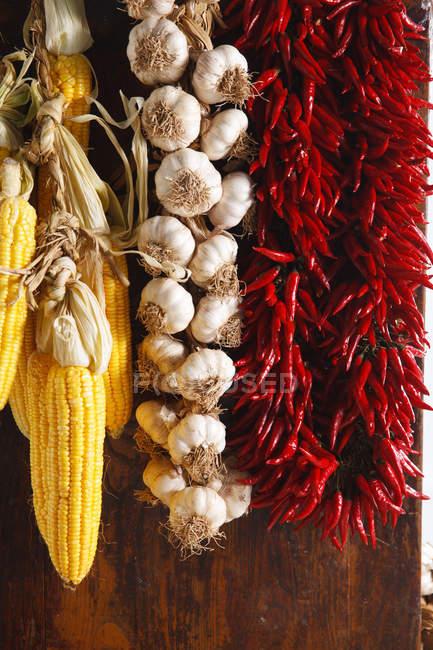 Vista de cerca de pimientos rojos, ajos y mazorcas de maíz colgando sobre fondo de madera - foto de stock