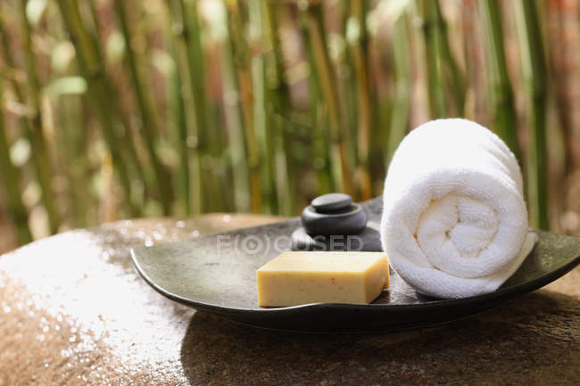 Close-up view of white rolled towel, soap and stones, spa concept — Stock Photo