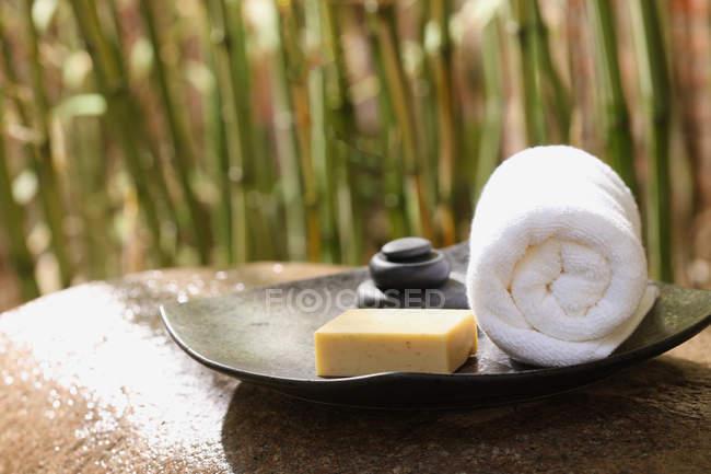 Вид на білий прокачений рушник, мило і камені, спа-концепція — стокове фото