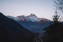 Belles montagnes enneigées et ciel bleu clair, maisons et arbres au premier plan — Photo de stock