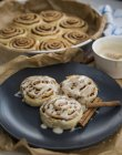 Close-up view of delicious sweet cinnamon rolls with cinnamon sticks on table — Photo de stock