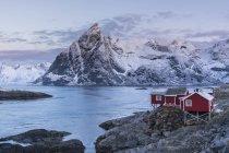 Beau paysage avec des montagnes enneigées et une hutte en bois sur des rochers près de l'eau — Photo de stock