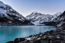 Beau paysage avec des montagnes enneigées et le lac calme — Photo de stock