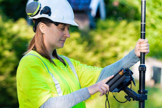 Side view of woman in hard hat and high-visibility clothing using engineering technology outdoor — Foto stock