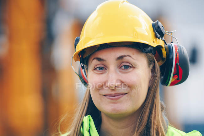 Happy female construction worker in yellow hard hat smiling at camera — Stockfoto