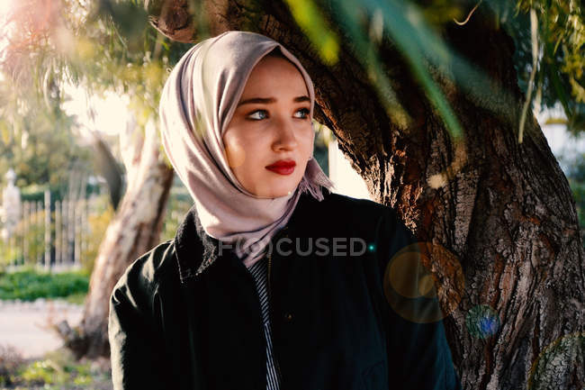 Young woman in gray hijab scarf and black jacket looking away outdoor — Stock Photo