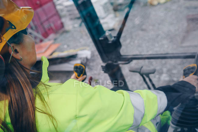 Cropped shot of woman in hard hat operating industrial vehicle — Stockfoto