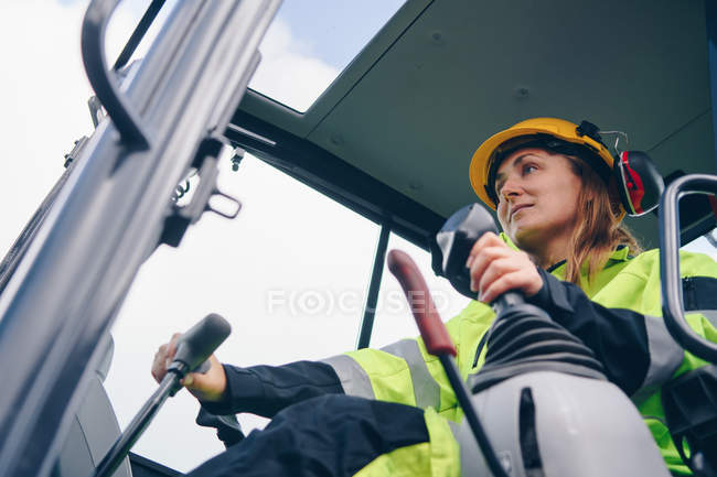 Low angle view of woman in hard hat and personal protective equipment operating industrial vehicle — Stockfoto