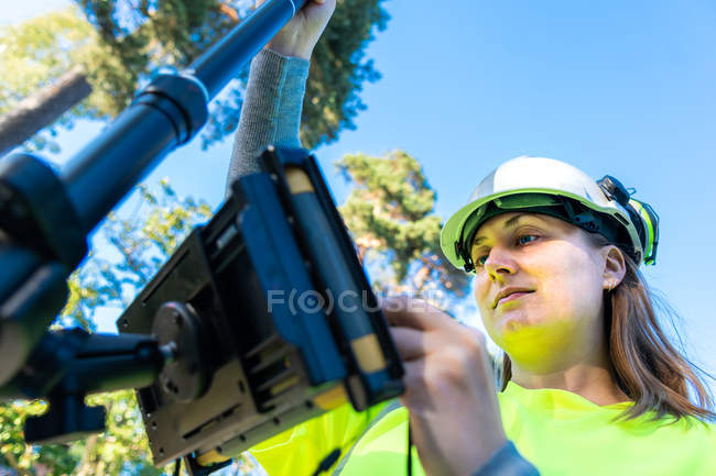 Low angle view of woman in hard hat and high-visibility clothing using engineering technology outdoor — Foto stock