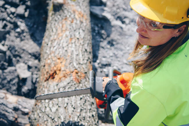 High angle view of woman in hard hat and protective goggles holding chainsaw and chopping wood — Stockfoto