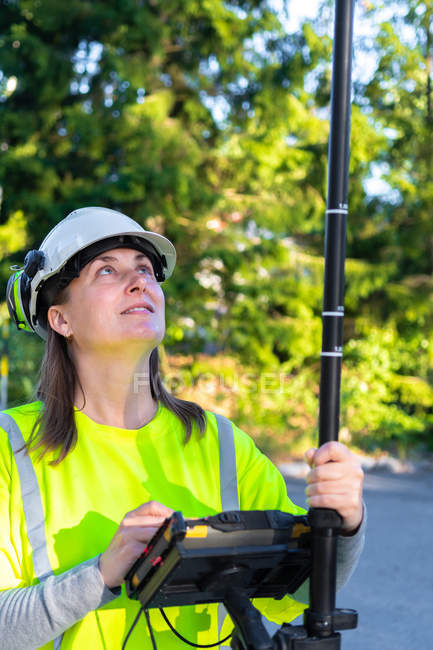 Woman in hard hat and high-visibility clothing using engineering technology outdoor — Foto stock