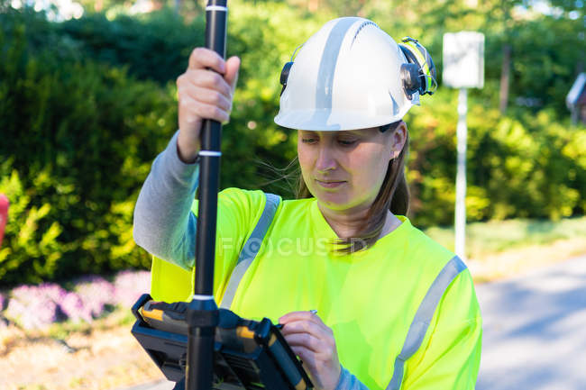 Woman in hard hat and high-visibility clothing using engineering technology outdoor — Stock Photo