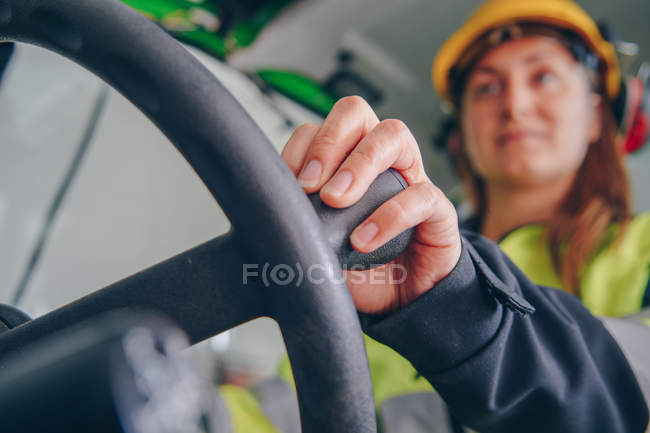 Low angle view of woman in hard hat and personal protective equipment operating industrial vehicle — Foto stock
