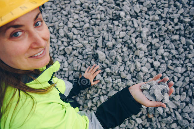 High angle view of female engineer holding rocks and smiling at camera — Stock Photo