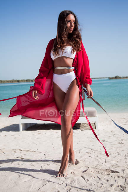Beautiful young barefoot woman in white swimwear and red robe walking on sandy beach — Stock Photo