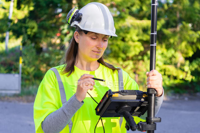 Woman in hard hat and high-visibility clothing using engineering technology outdoor — Stockfoto