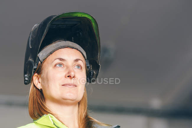 Close-up view of woman wearing black helmet and looking away at construction site — Foto stock