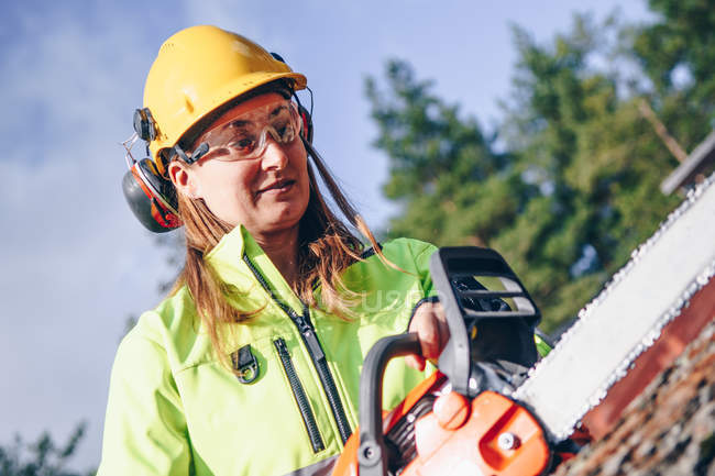 Woman in hard hat and protective goggles holding chainsaw and chopping log — Stock Photo