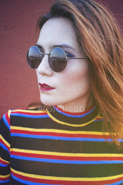Portrait of beautiful young woman in striped turtleneck and sunglasses looking away — Stock Photo