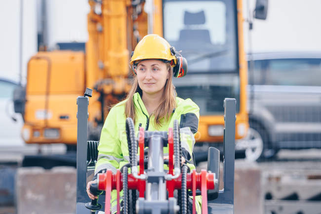 Woman in hard hat and personal protective equipment operating industrial vehicle — Foto stock
