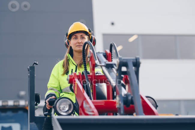 Woman in hard hat and personal protective equipment operating industrial vehicle — Stock Photo