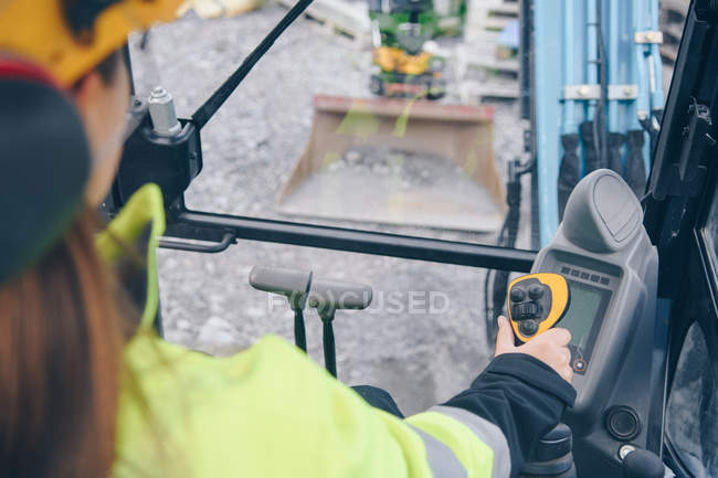 Cropped shot of woman in hard hat operating industrial vehicle — Stock Photo