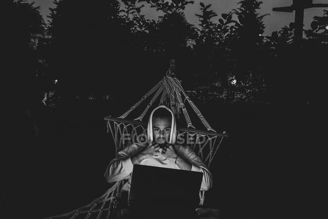 Black and white image of young man lying in hammock and using laptop — Stock Photo