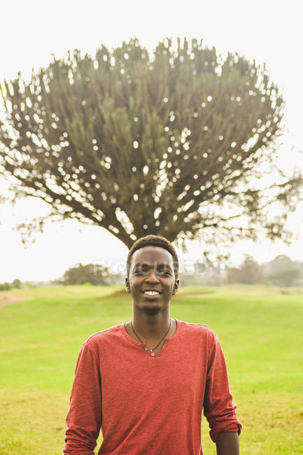 Handsome smiling young man standing beside green leafed tree — Fotografia de Stock