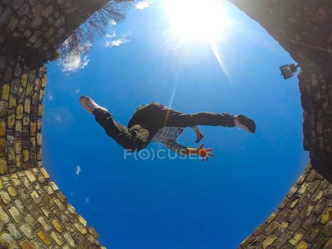 Vista in basso dell'uomo saltando bene contro cielo azzurro — Foto stock