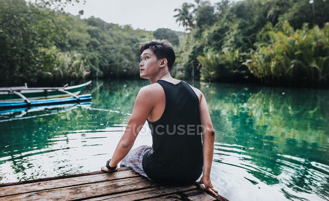 Back view of handsome young man sitting on wooden boat and looking up — Fotografia de Stock