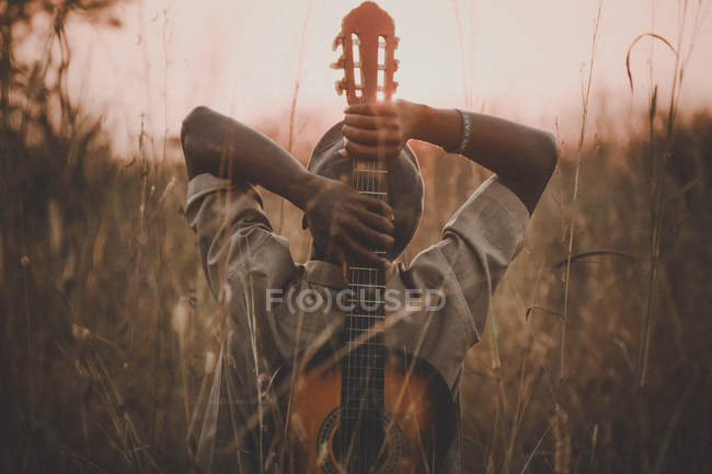Back view of man holding classical guitar while sitting on grass field — Stock Photo